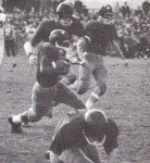 Woody White takes the ball for a ride against Clark '63 season. Notice the leather helmets.